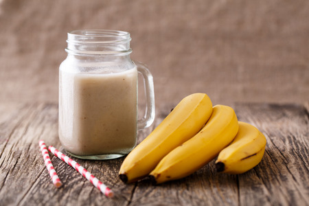 61024238 - delicious banana smoothie in glass jar with drinking straw and bananas on table.
